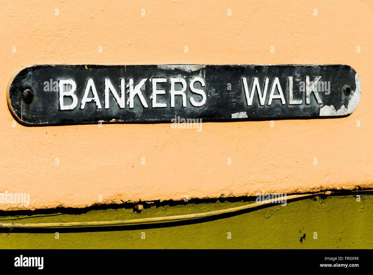 Street sign, 'Bankers Walk' on a grungy house wall. - Stock Image