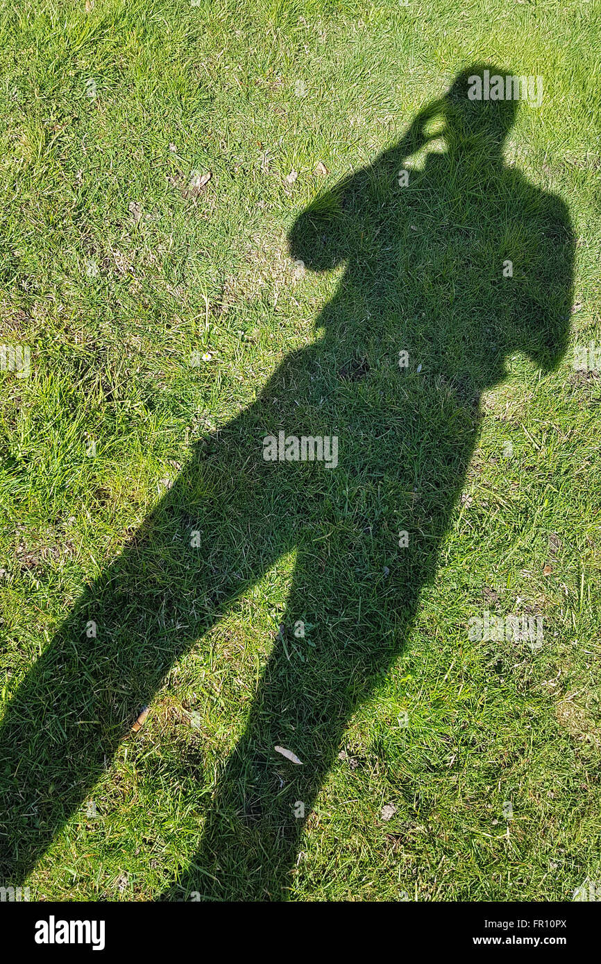 Stress, headache, health care and people concept: man's shadow projected on green grass with hand to his head - Stock Image