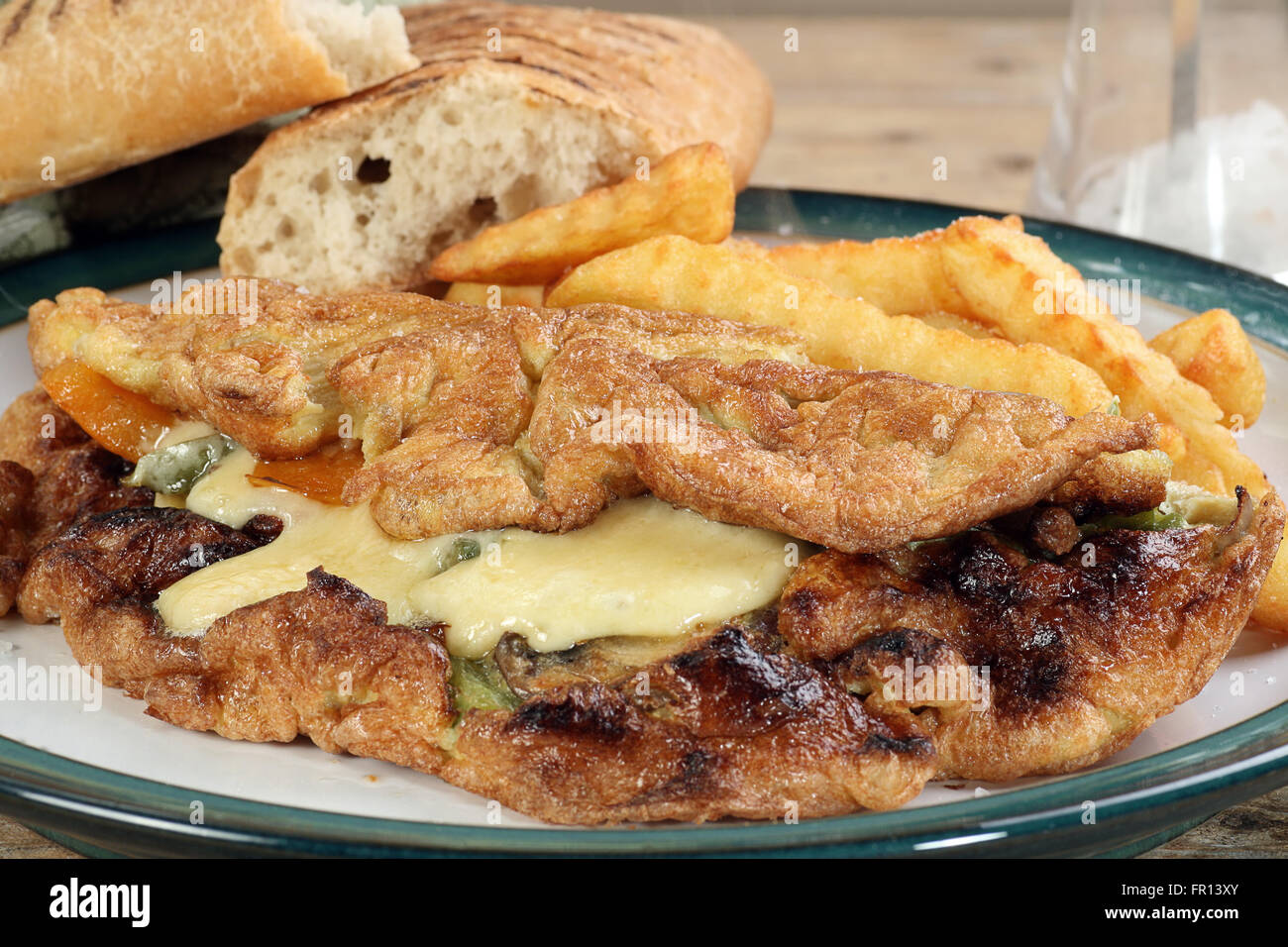 cheese mushroom and sweet pepper omelette with fries - Stock Image