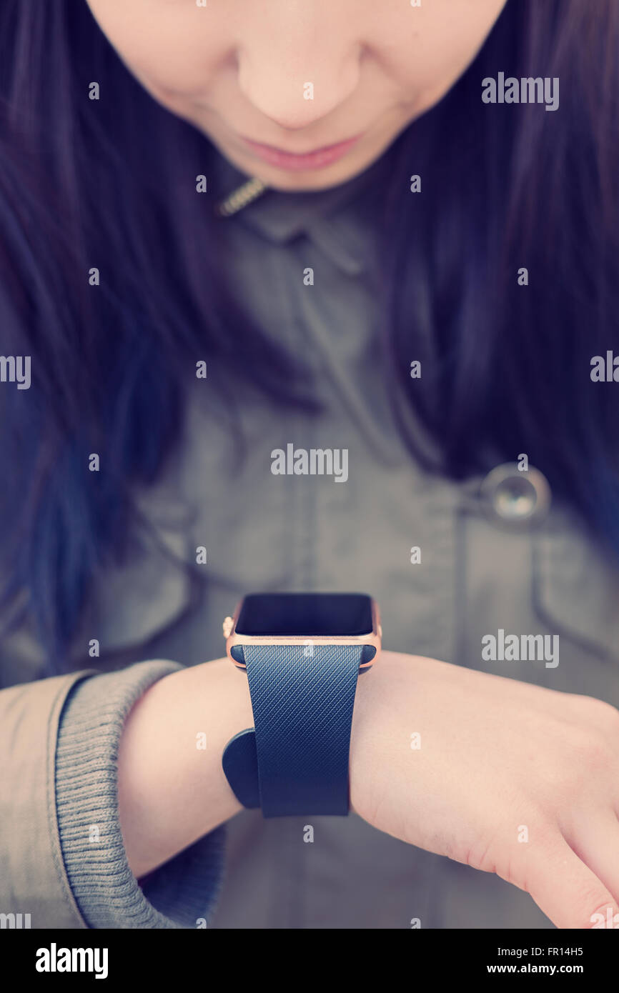 Young girl checking new messages on her trendy smart wrist watch. This person is always connected to social media - Stock Image