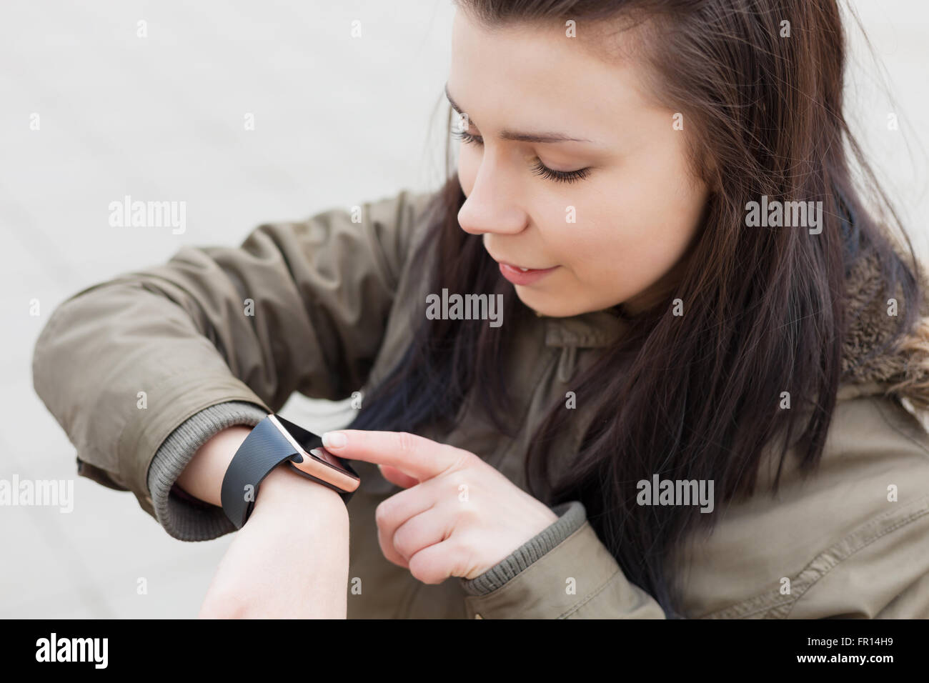 Young girl using her modern smart wrist watch. She is always connected to social media and internet. - Stock Image