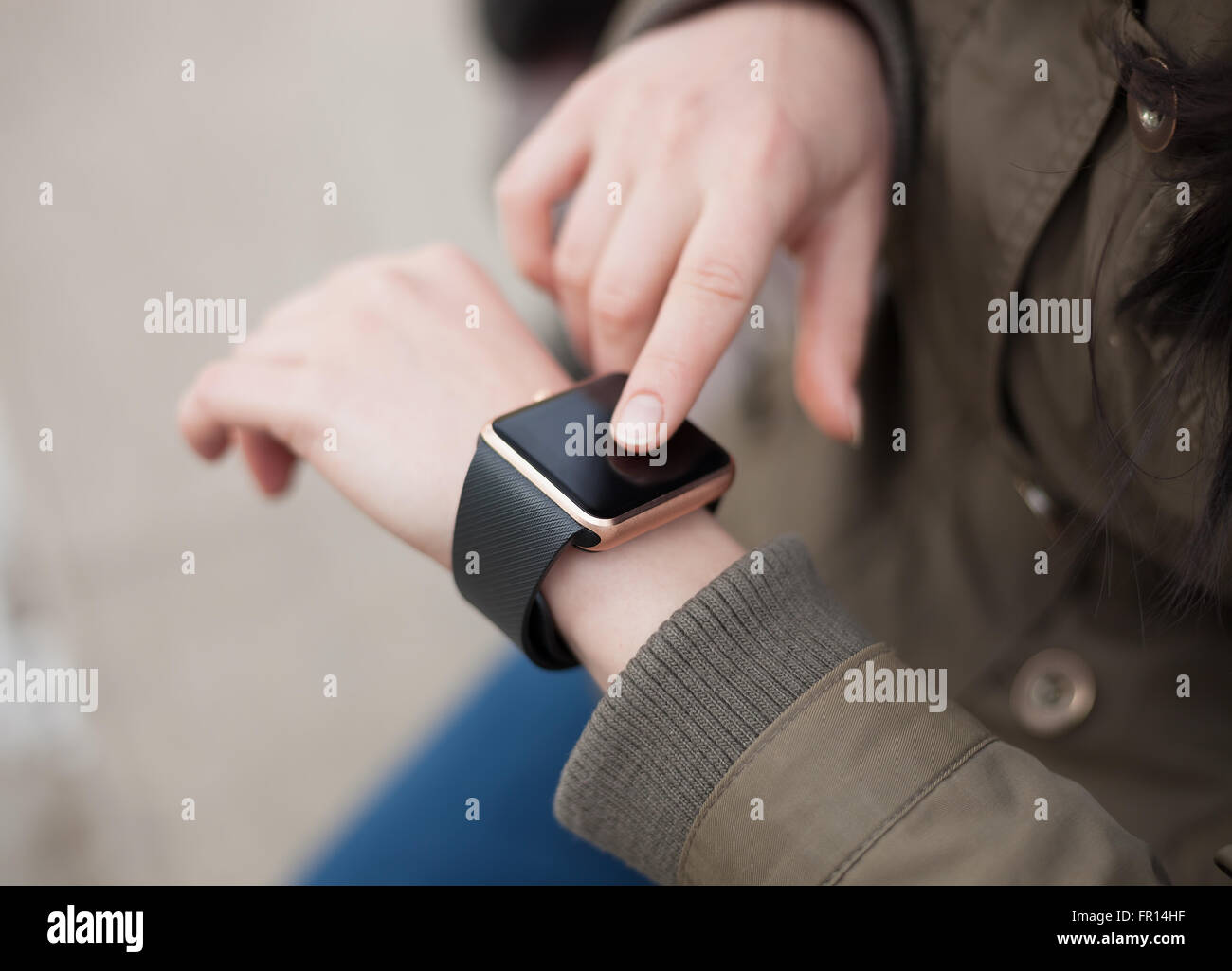Female touching on her trendy smart wrist watch. This person is always connected to social media and internet. - Stock Image