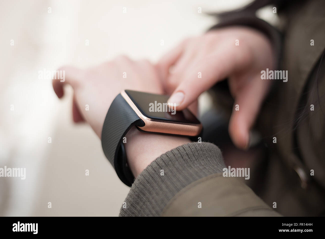 Hands of a female using her trendy smart wrist watch. This person is always connected to social media and internet. - Stock Image