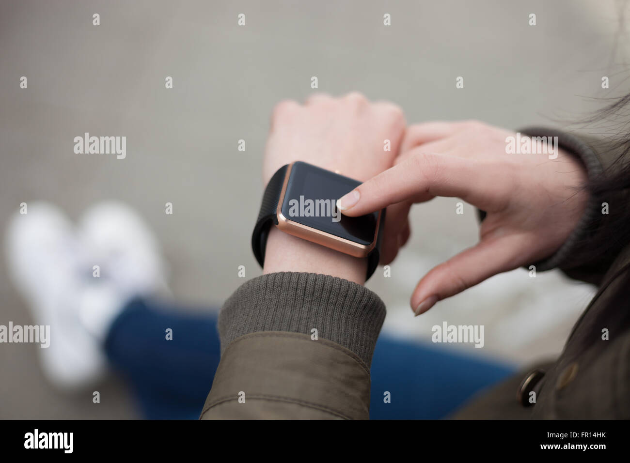Young girl browsing new messages on her trendy smart wrist watch. This person is always connected to social media - Stock Image