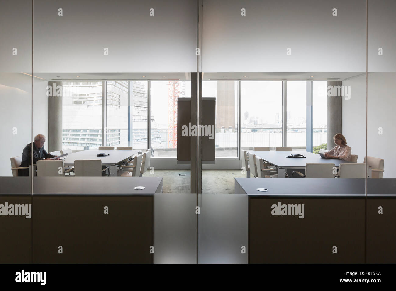 Business people working in modern symmetrical conference rooms - Stock Image