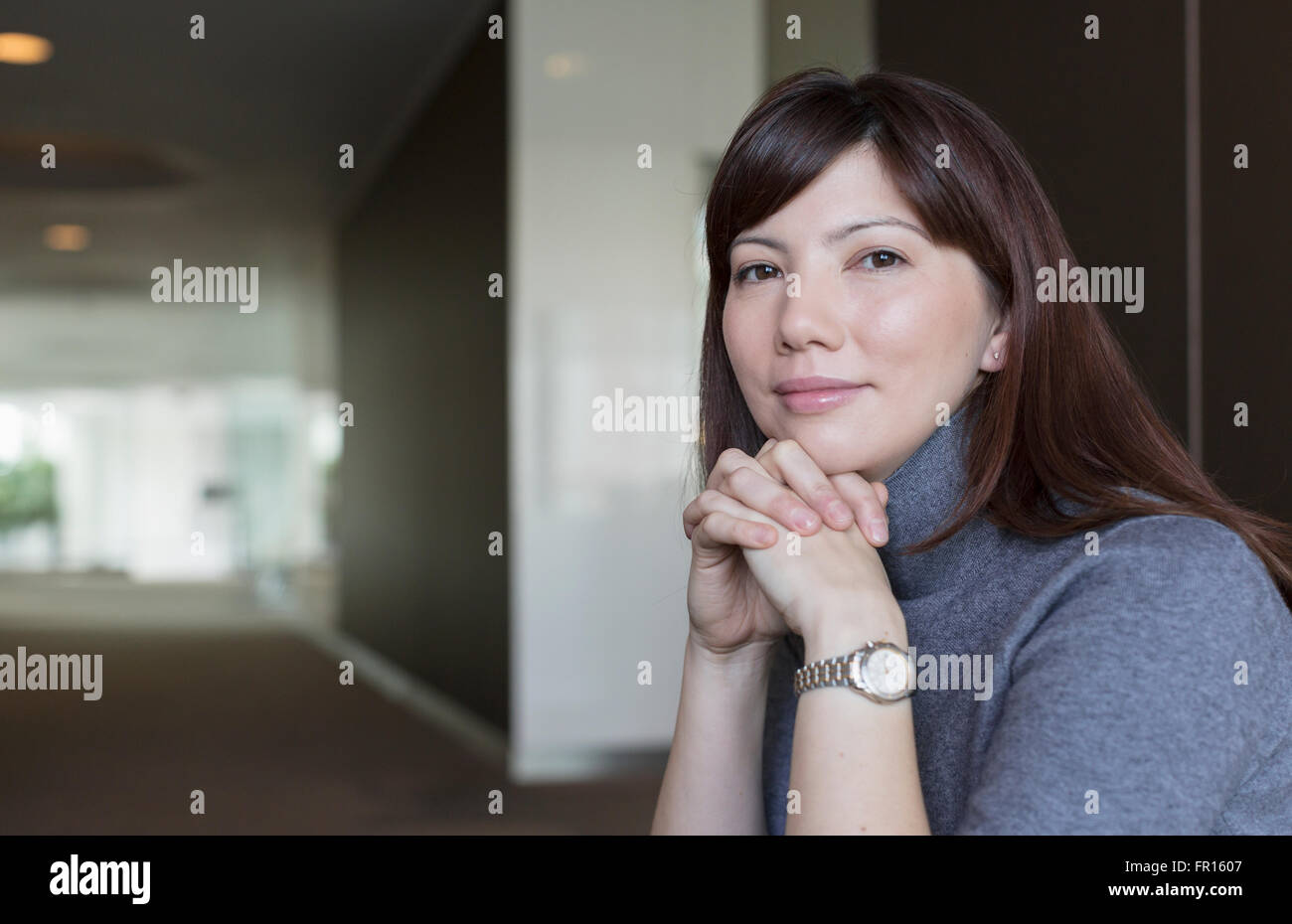 Portrait confident businesswoman with hands clasped - Stock Image