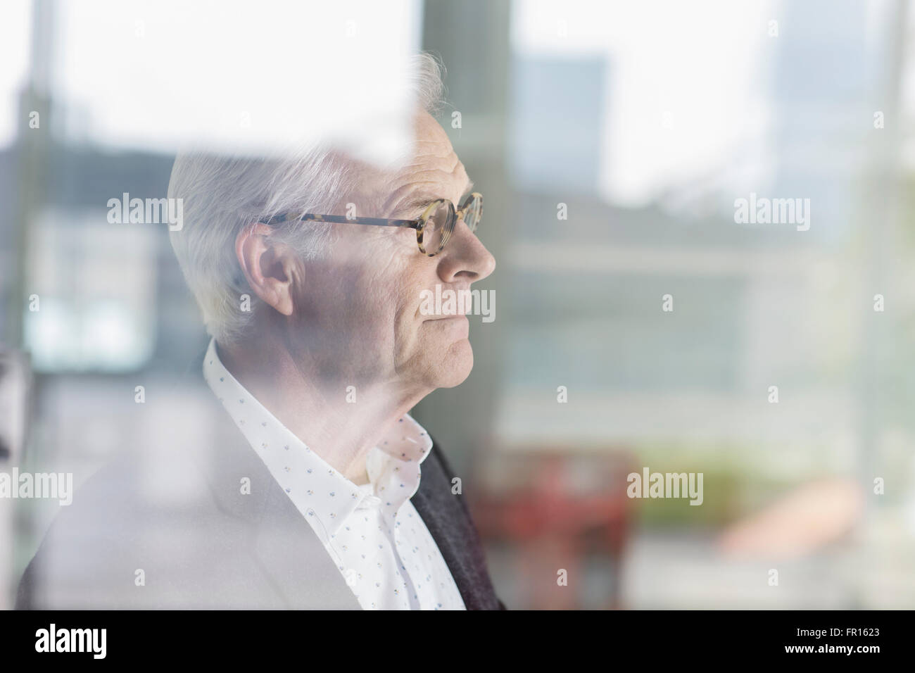 Pensive senior businessman looking out office window - Stock Image