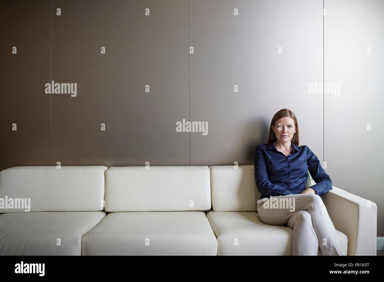 Portrait confident businesswoman with legs crossed on sofa - Stock Image
