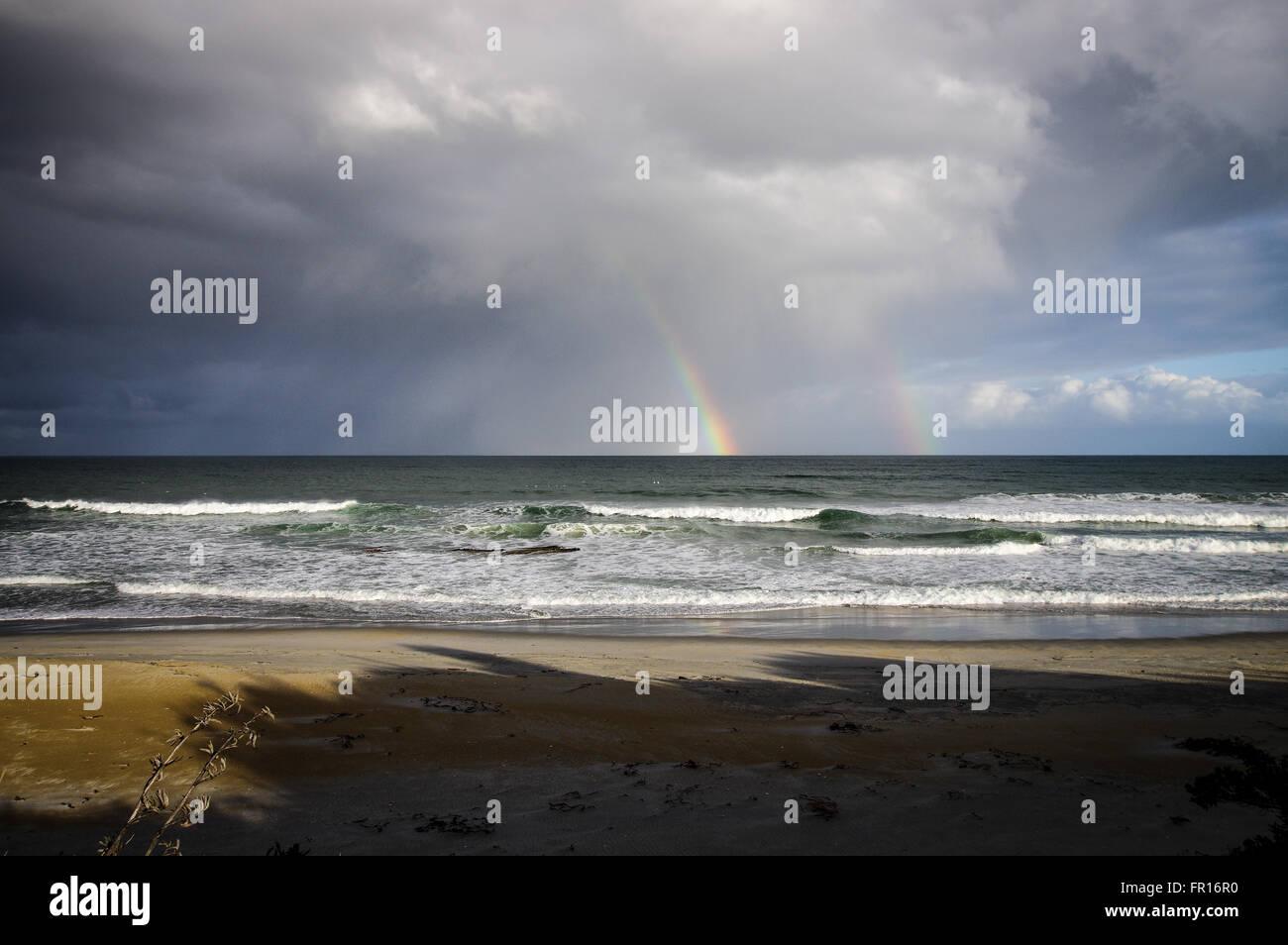 Double rainbow over Kuri Bush Beach - Otago, New Zealand Stock Photo