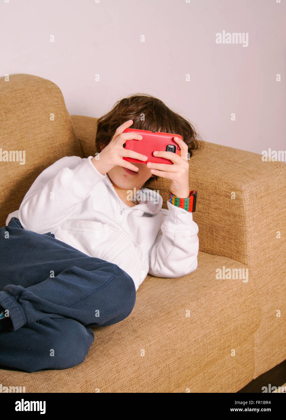 elementary school boy engrossed in a game on a mobile phone on the sofa - Stock Image
