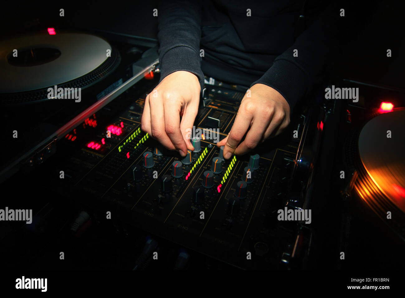 Hands of a female DJ mixing two tracks on professional audio equipment - Stock Image