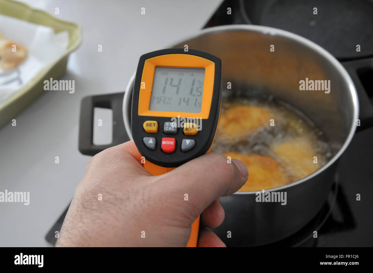 Handheld laser remote thermometer measures the temperature of boiling oil 141 degrees Celsius - Stock Image