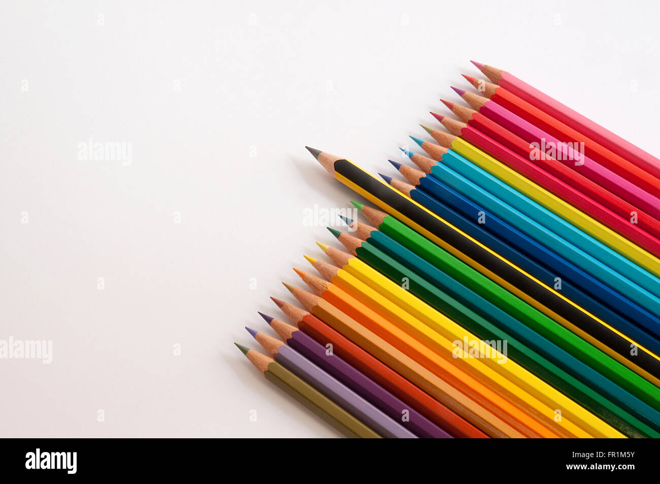Graphite pencil sticking out from coloured pencils. - Stock Image