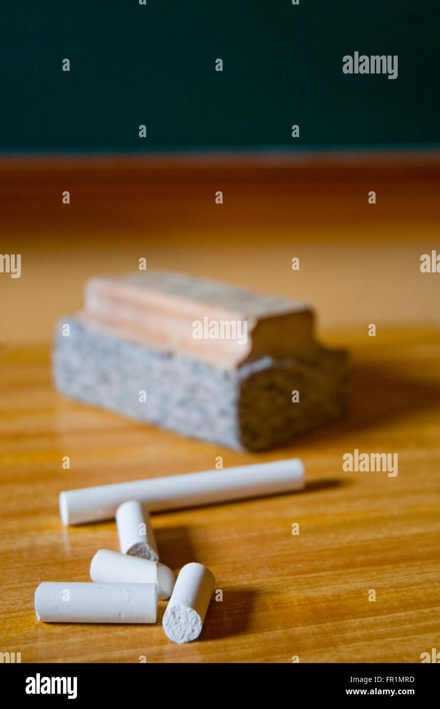 Chalks and board duster on teacher's table. Stock Photo