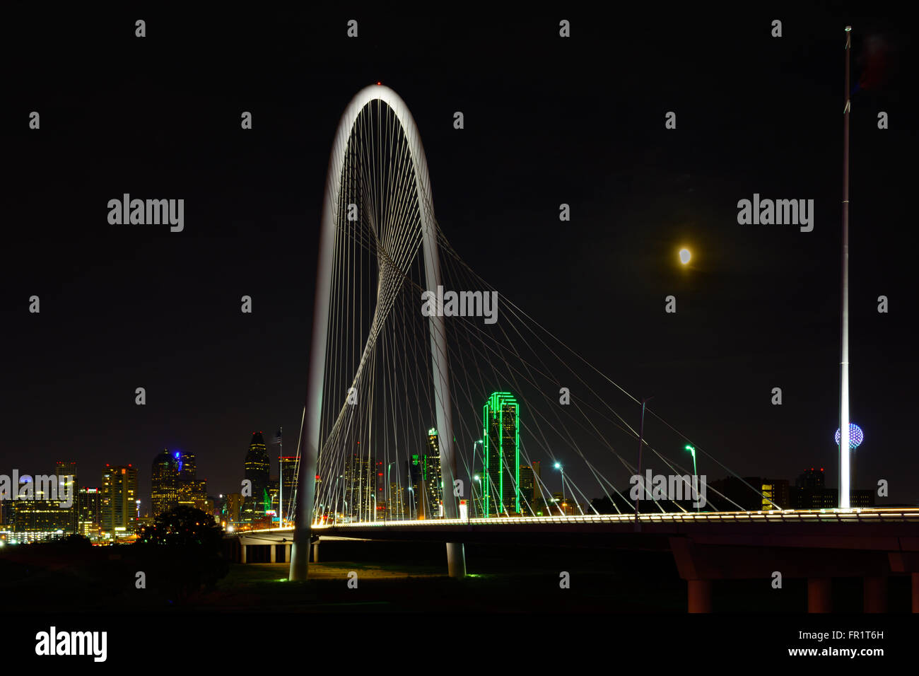 Dallas, Texas Skyline Nightscape with bridge in the foreground and moon in sky. Margaret Hunt Hill Bridge Showcases - Stock Image
