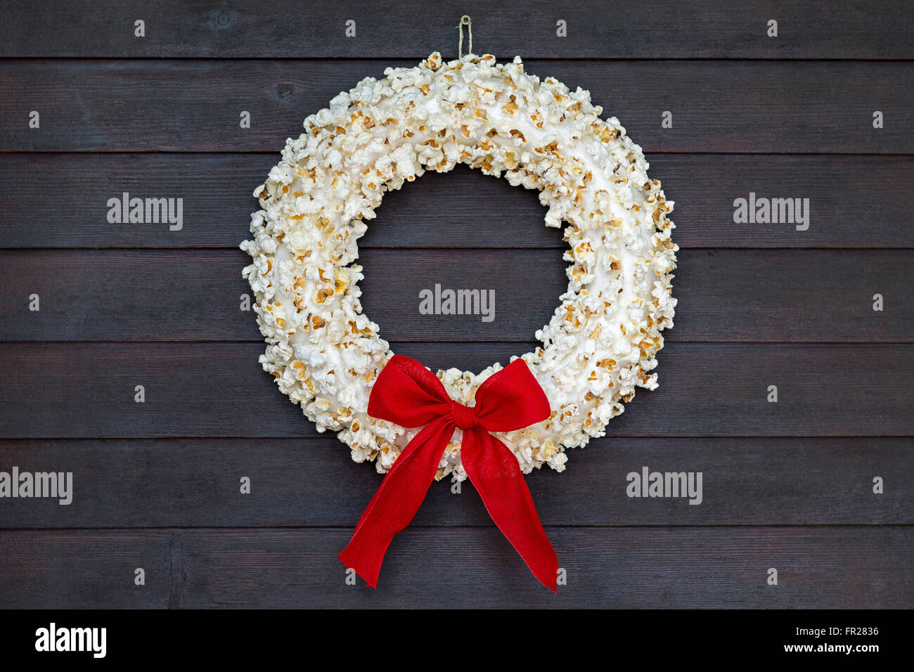 Popcorn wreath with red bow hanging on dark wooden door - Stock Image