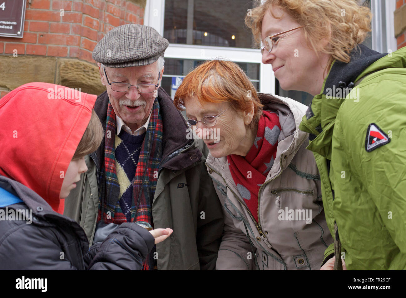 grandparents and mother admiring what child is showing them - Stock Image