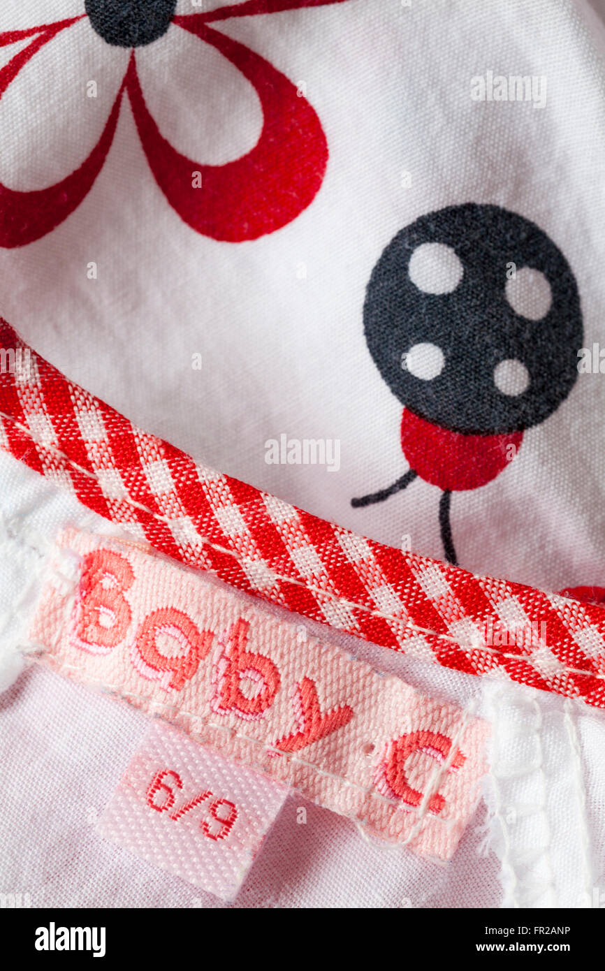 Baby C label in baby girl's dress age 6/9 months - Stock Image