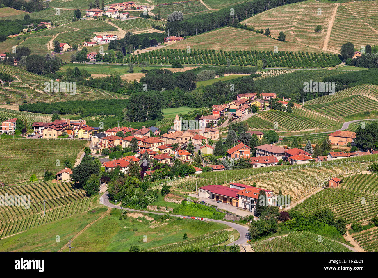 Small town among green hills of Piedmont, Northern Italy. - Stock Image