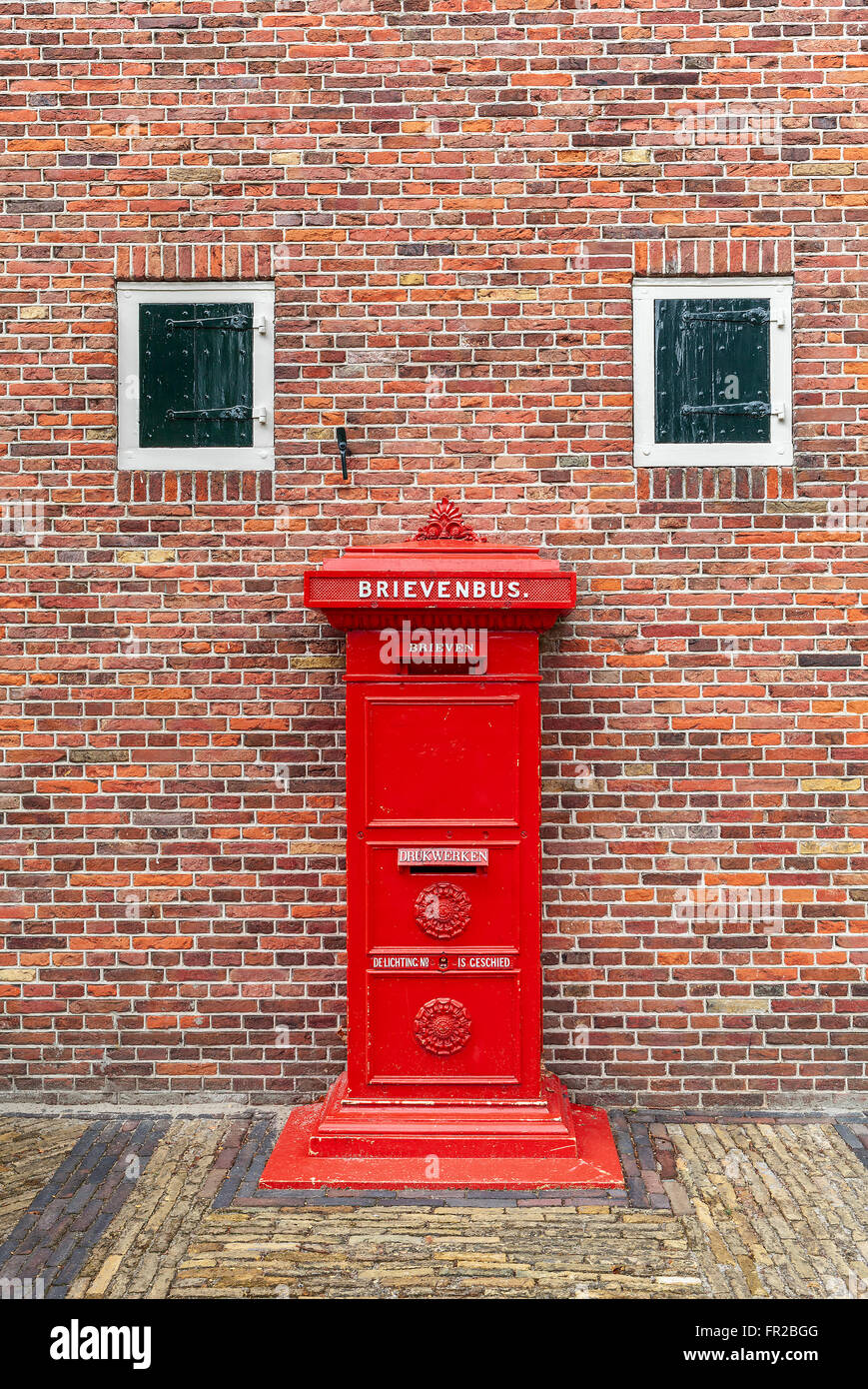 Old red postbox in front of brick wall in Zaanse Schans, Netherlands. - Stock Image