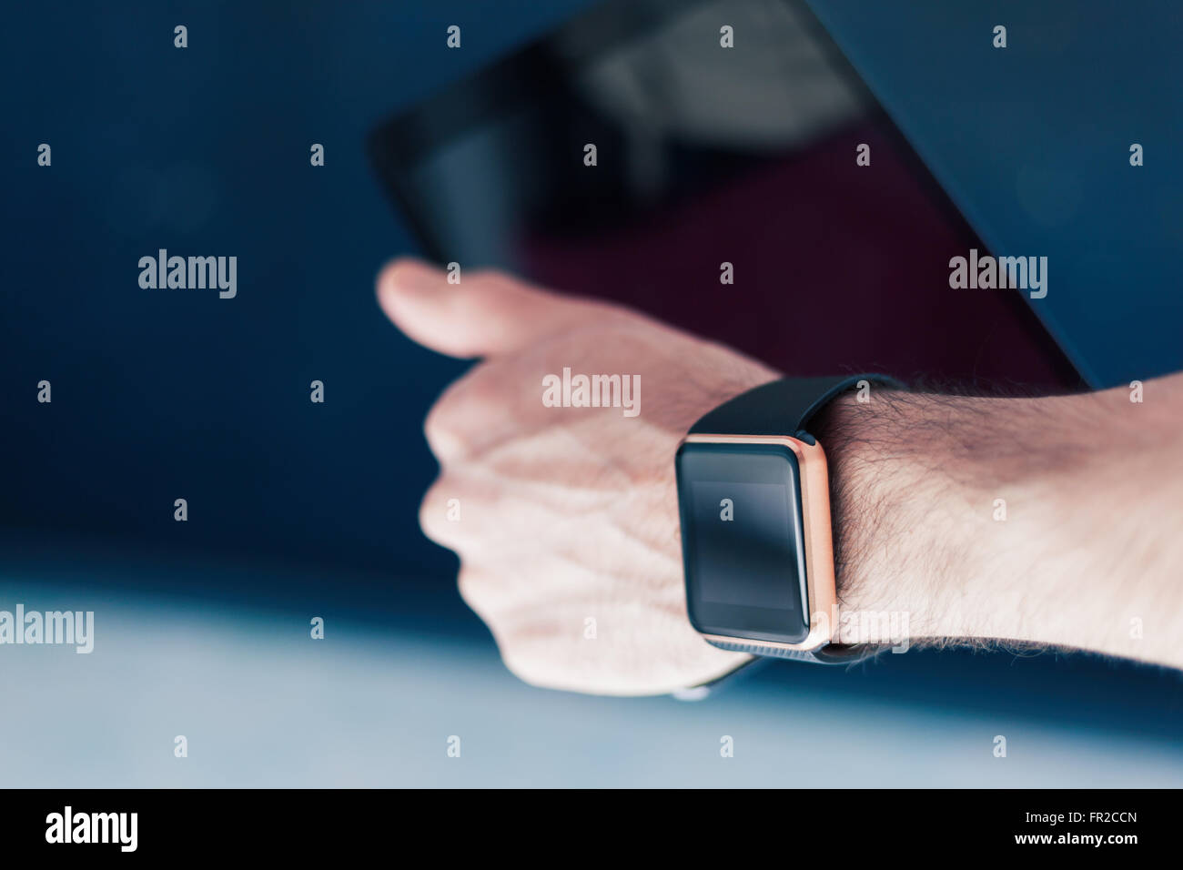 Male hand with two devices on it - trendy smart watch and tablet pc. This person is always connected to internet - Stock Image