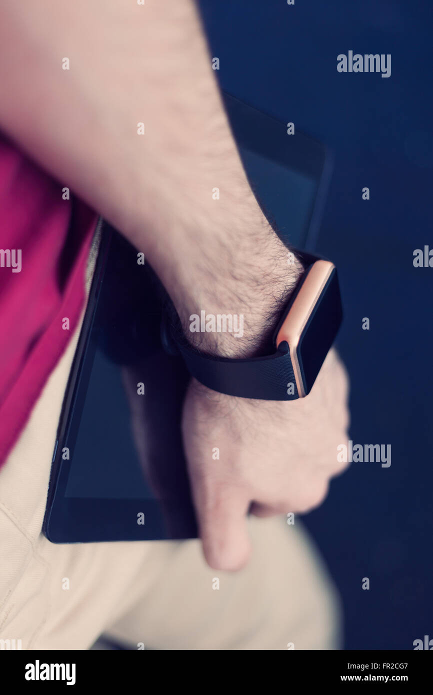 Male hand holding smart wrist watch and tablet pc. Modern stylish gadgets to be always connected. Vertical orientation, - Stock Image