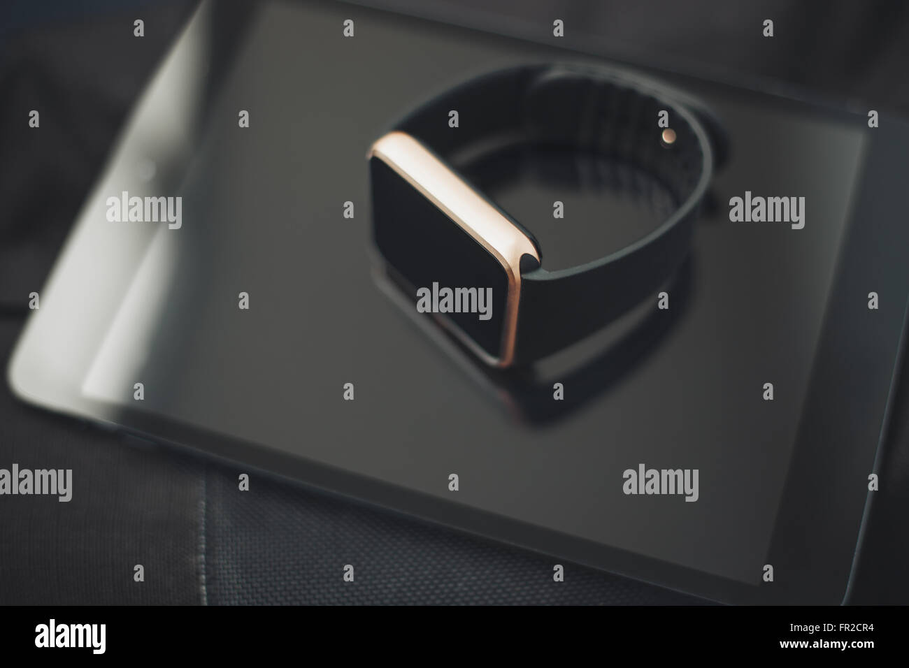 Smart wrist watch laying on a tablet pc. This gadgets will let you always stay connected to the social media, internet - Stock Image