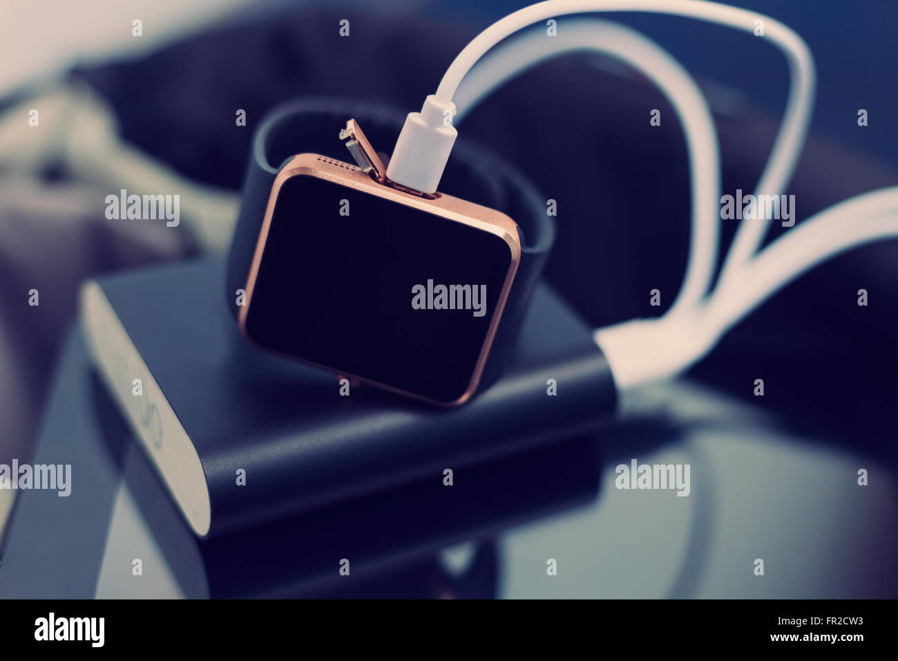 Smart wrist watch charging from a travel powerbank charger. Travel and stay connected to the media networks anywhere - Stock Image