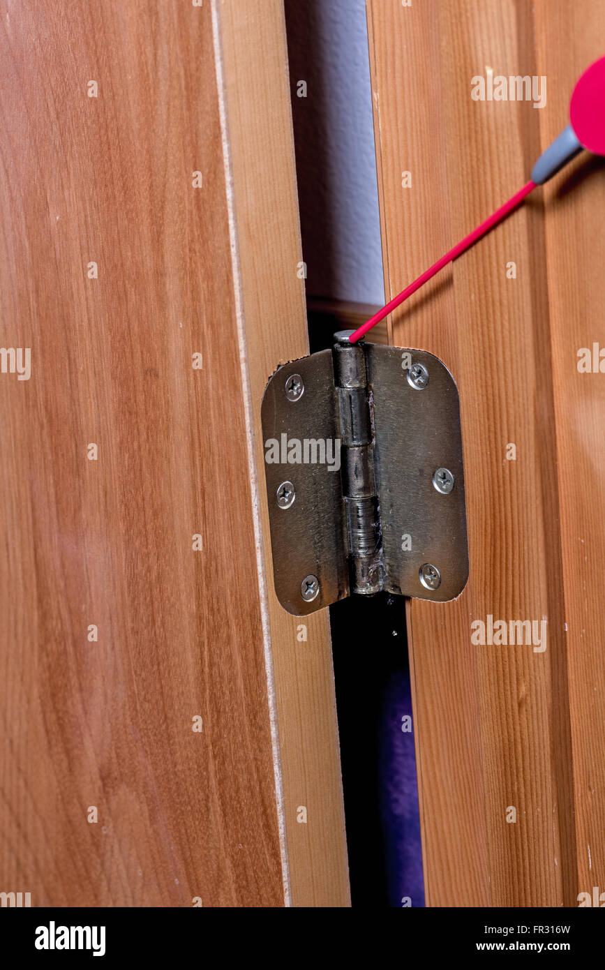 Spray oil is applied to a door hinge - Stock Image
