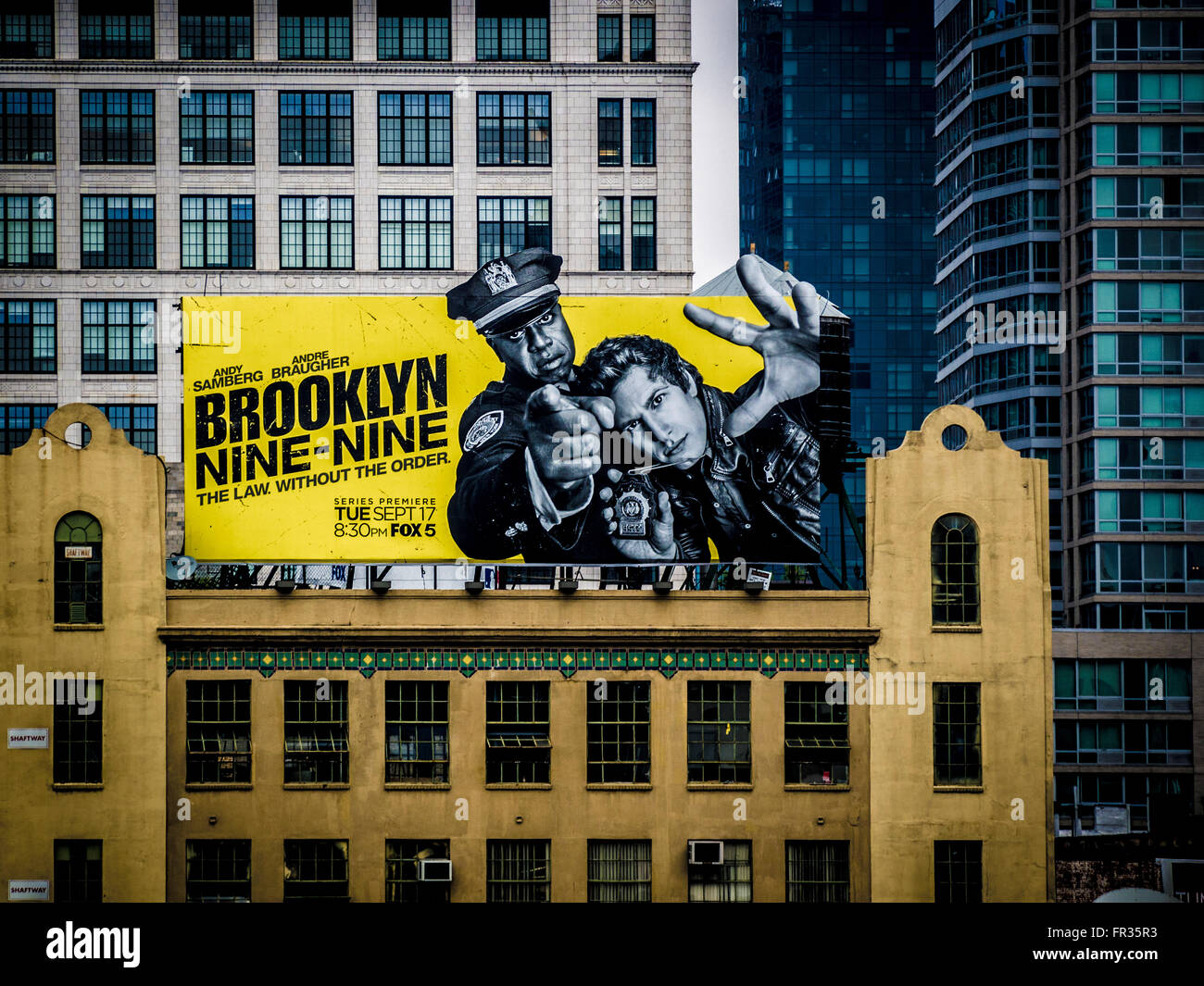 Brooklyn Nine-Nine advertising billboard on roof of traditional buildings, New York City, USA. - Stock Image