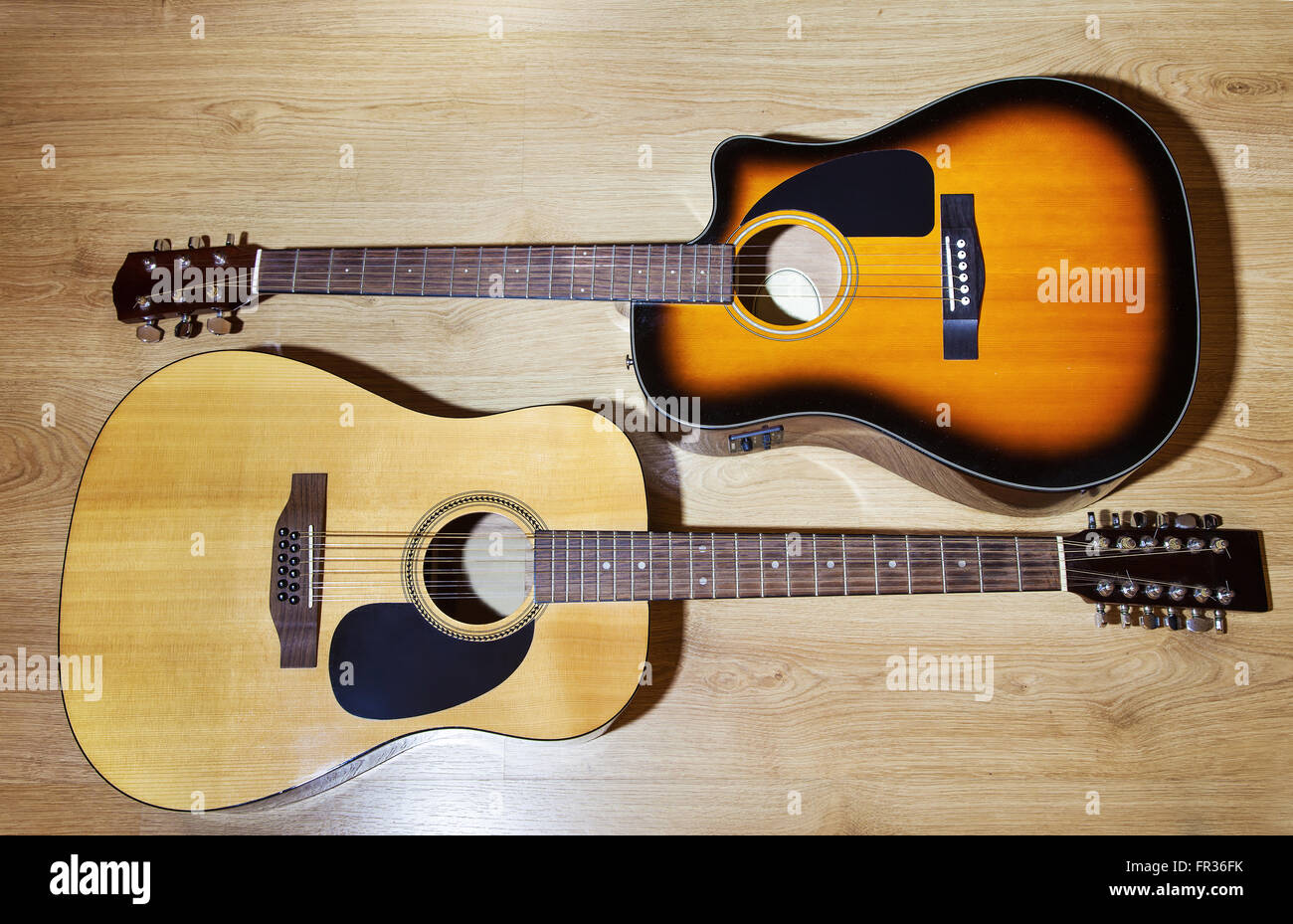 two acoustic guitars lying on wooden floor closeup - Stock Image