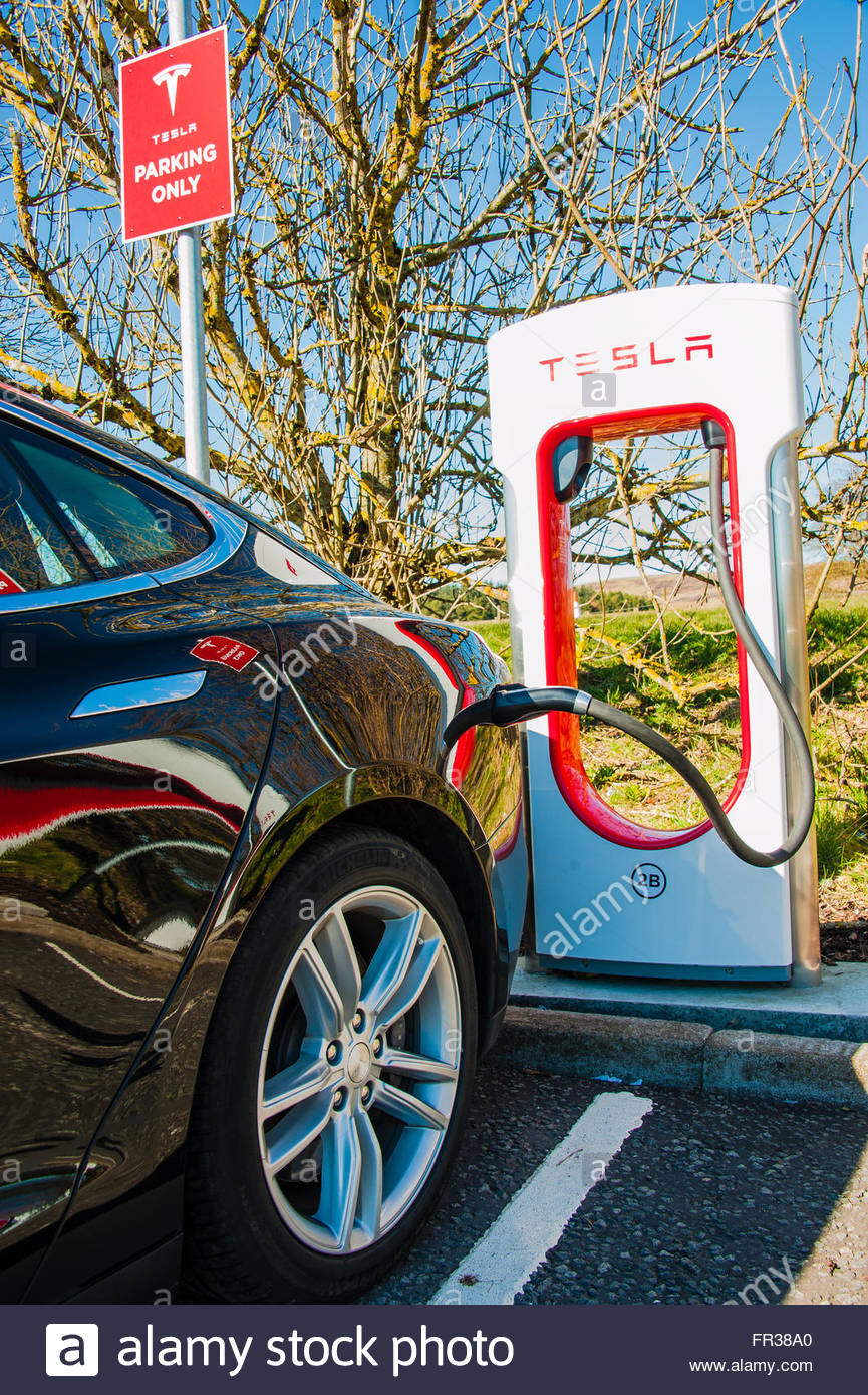 A Black Tesla Model S Electric car being charged on the electric car charging units on the forecourt at Abington Stock Photo