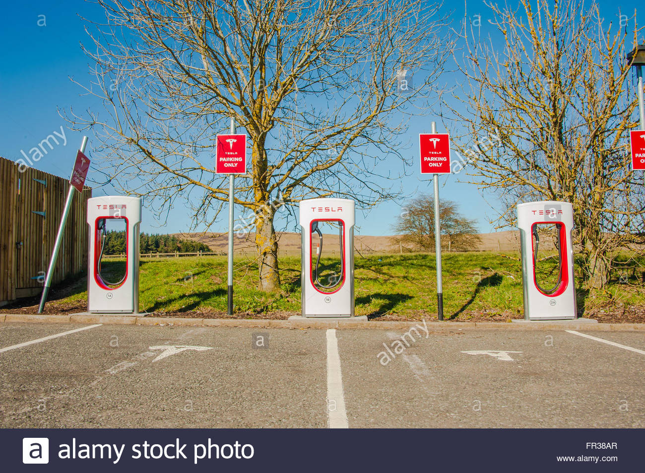 A row of three Tesla electric car charging units on the forecourt at Abington Services, just off the M74 in Scotland - Stock Image