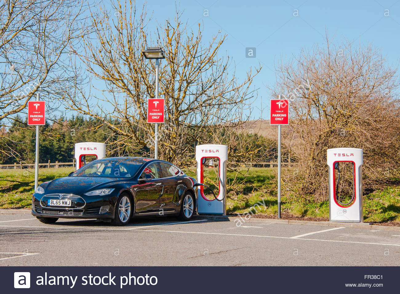 A Black Tesla Model S Electric car being charged on the electric car charging units on the forecourt at Abington - Stock Image