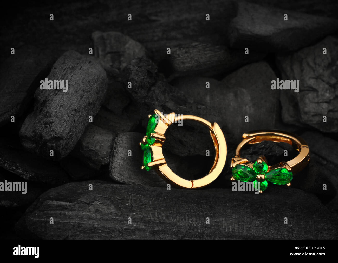 jewelry earring s witht gem emerald on dark coal background - Stock Image