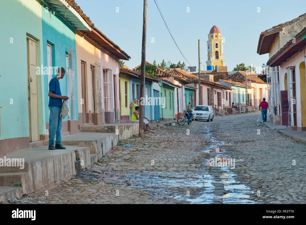A street in the old colonial town of Trinidad, Cuba with the Iglesia y Convento de San Francisco in the background. - Stock Image