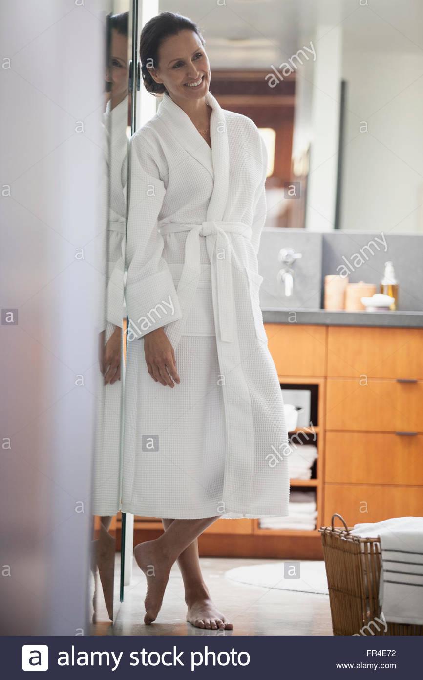 woman in robe standing in doorway - Stock Image