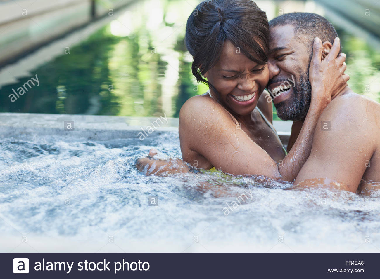 couple holding each other and laughing in hot tub - Stock Image