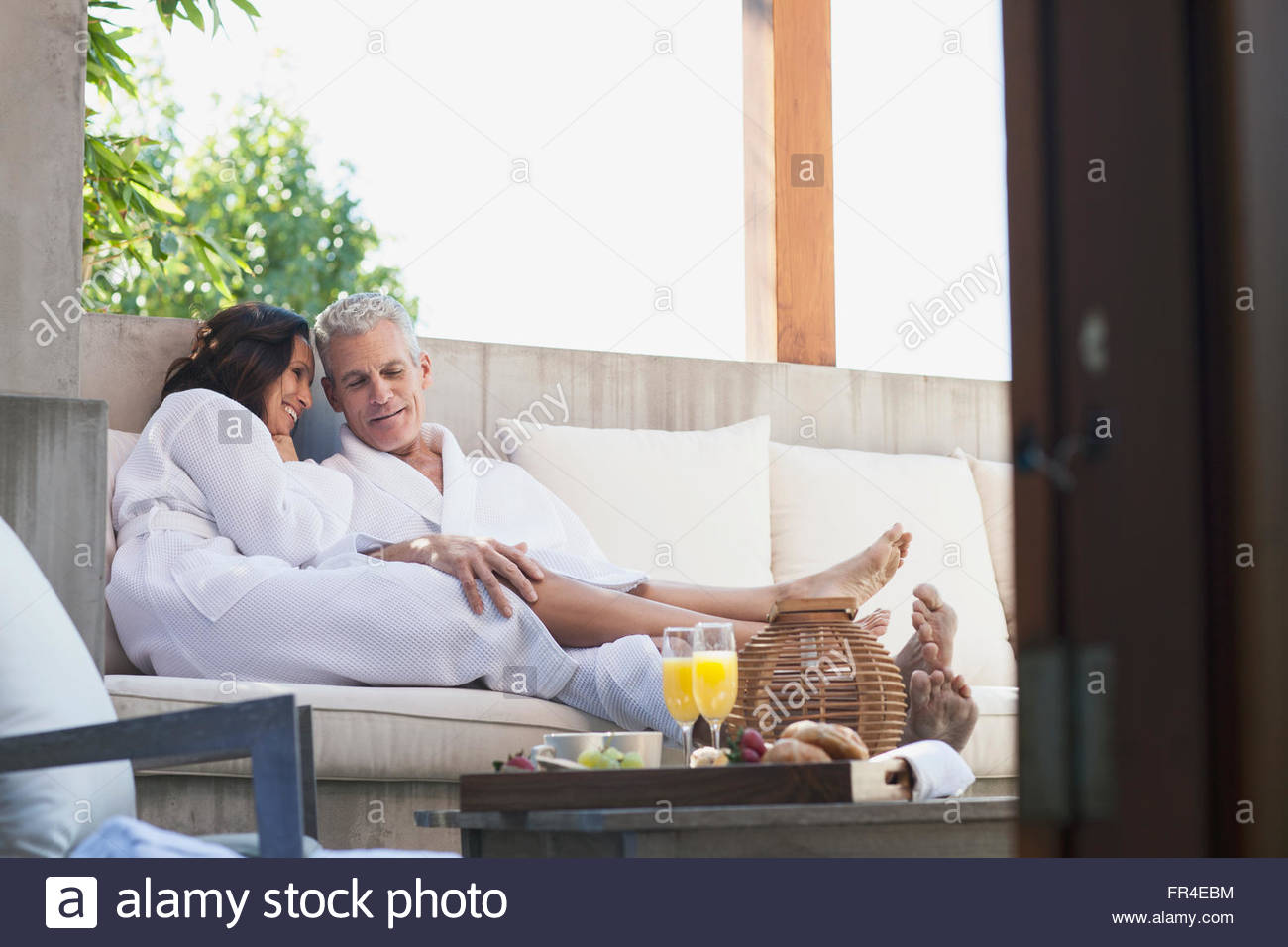couple in robes talking on outdoor patio - Stock Image