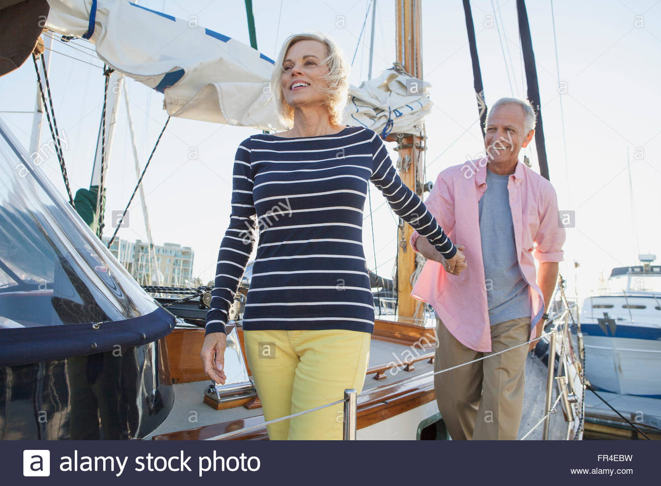 senior couple walking on boat dock - Stock Photo