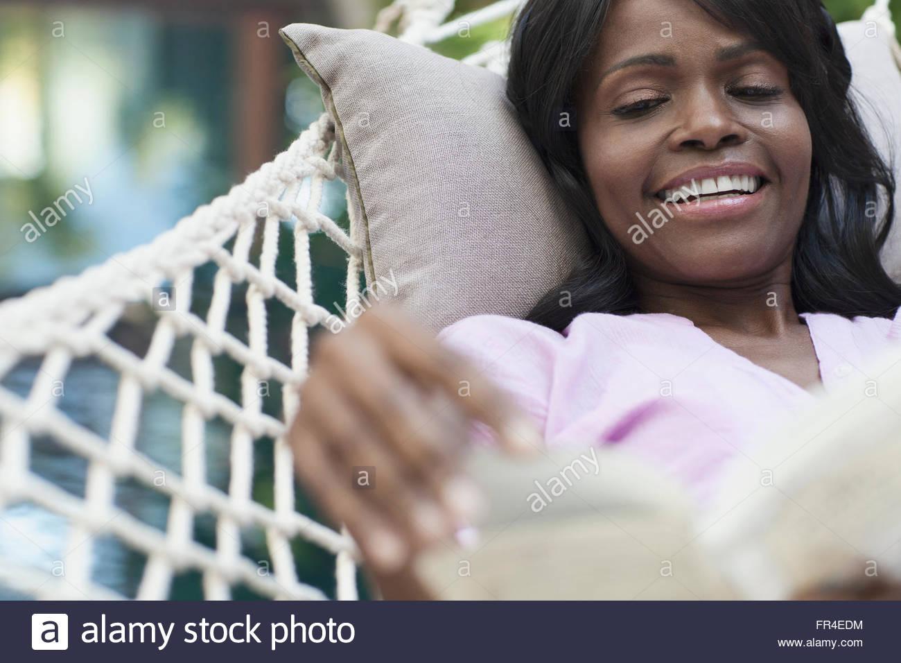 Beautiful african american woman with book in hammock - Stock Image