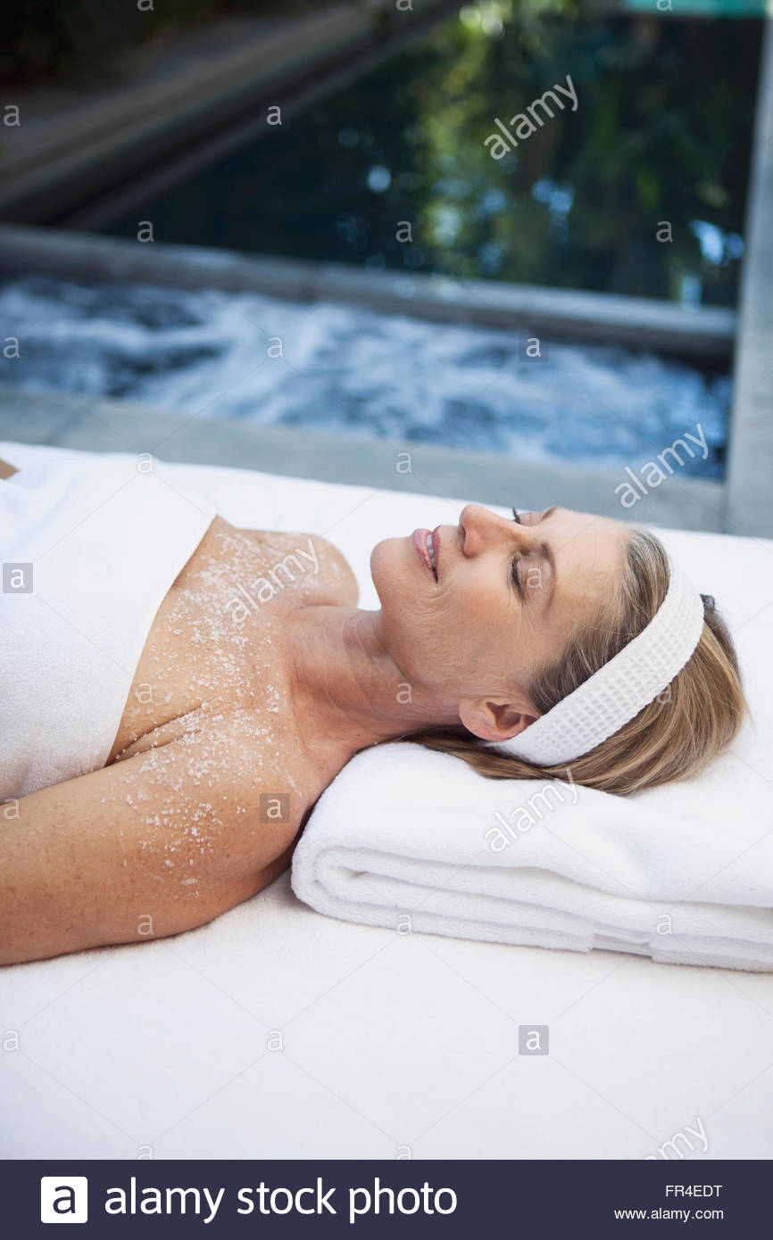 middle aged woman enjoying salt scrub treatment - Stock Image