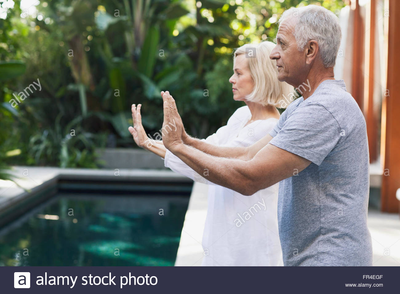 senior couple doing Tai Chi by pool - Stock Image