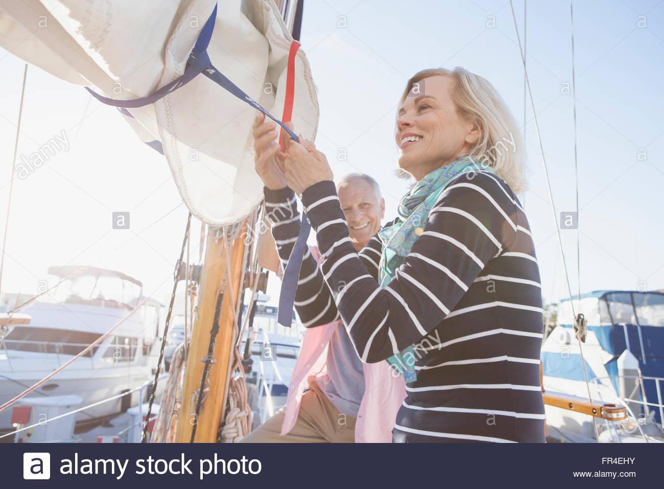 senior woman adjusting mainsail on sailboat - Stock Image