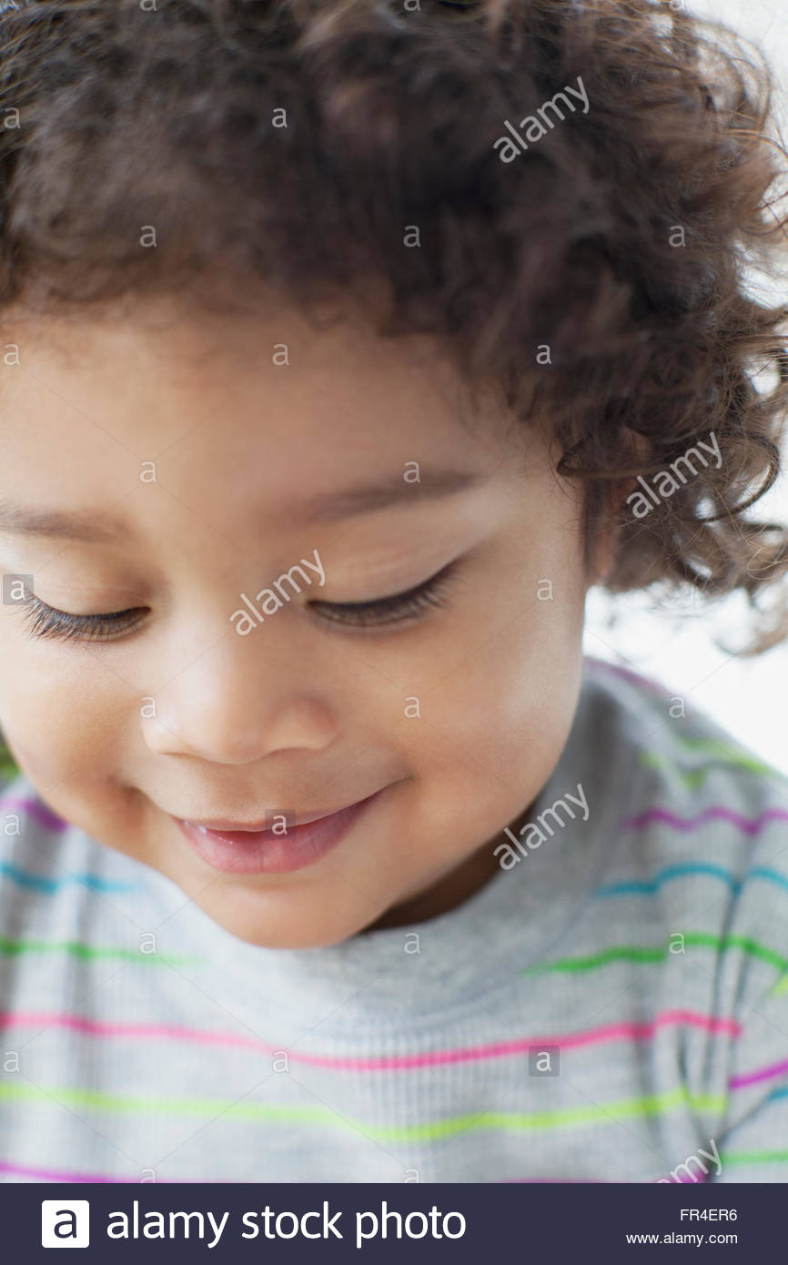 close up of curly haired toddler looking down - Stock Image