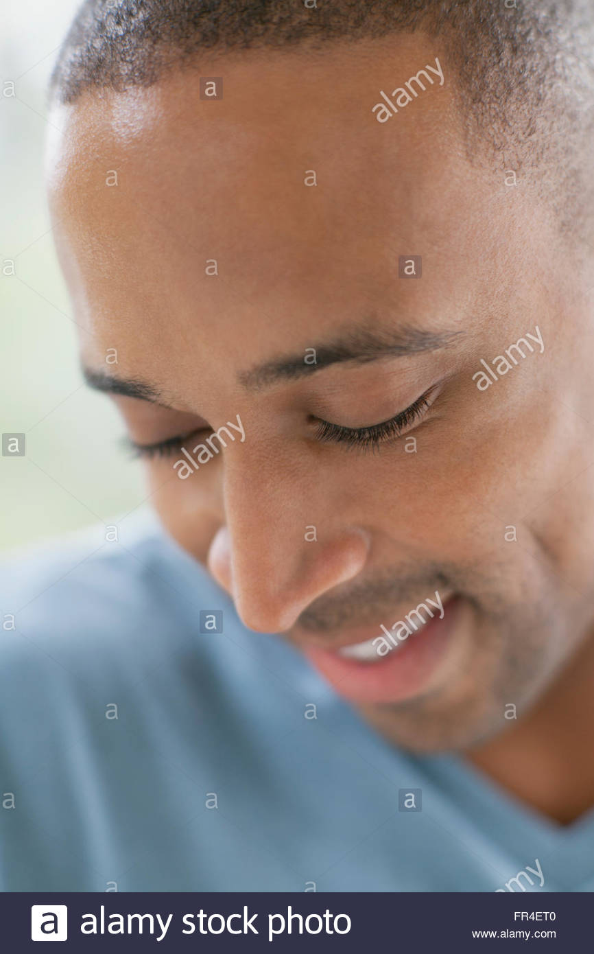 close up of mid adult man with head bowed - Stock Image