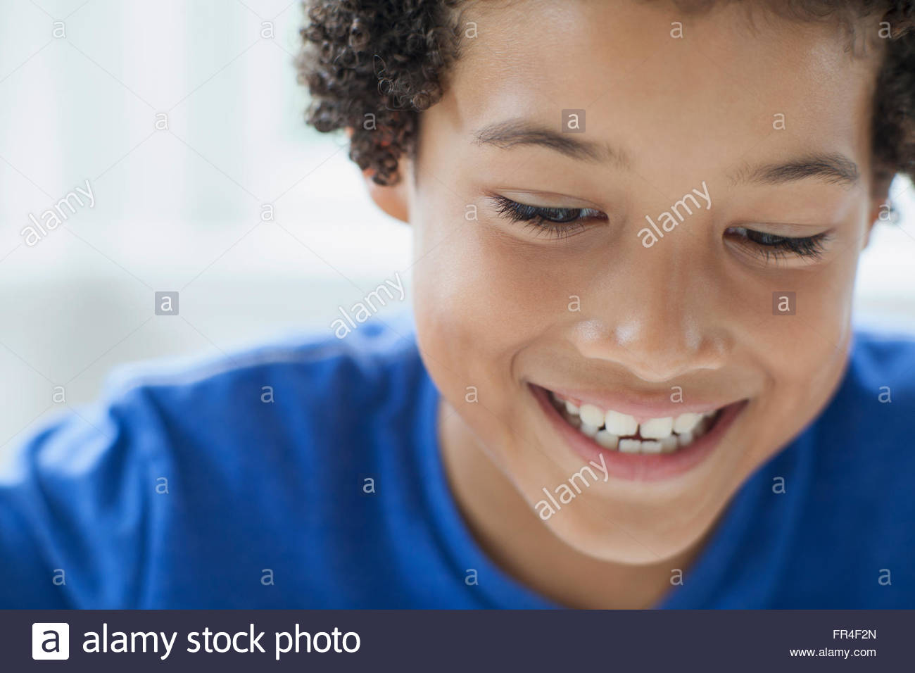 close up of cute preteen boy looking down - Stock Image
