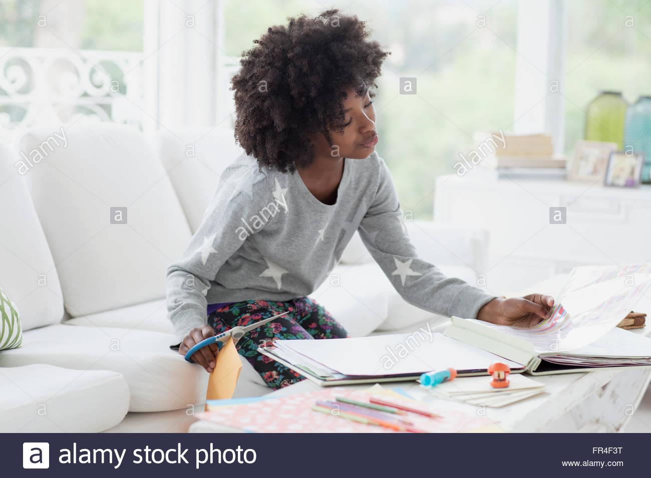 preteen girl working on scrapbook - Stock Image