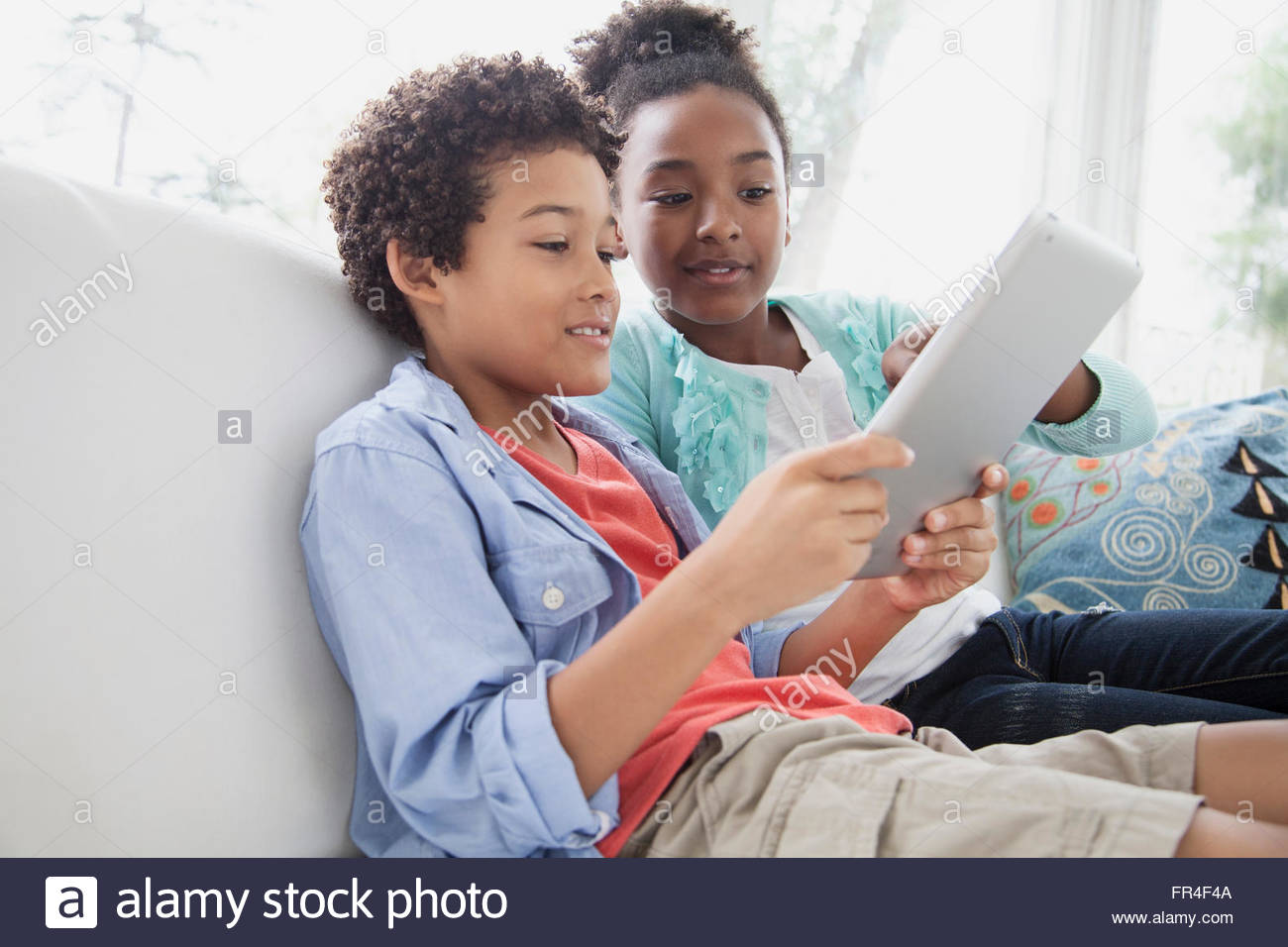 preteen brother and sister playing on pc tablet together - Stock Image