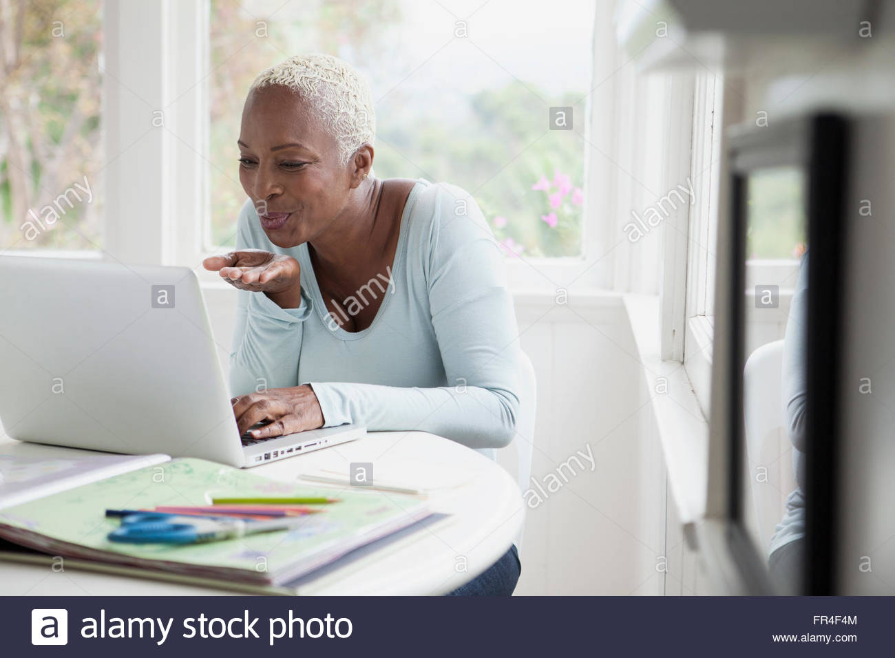 middle aged woman blowing kisses during online chat - Stock Image